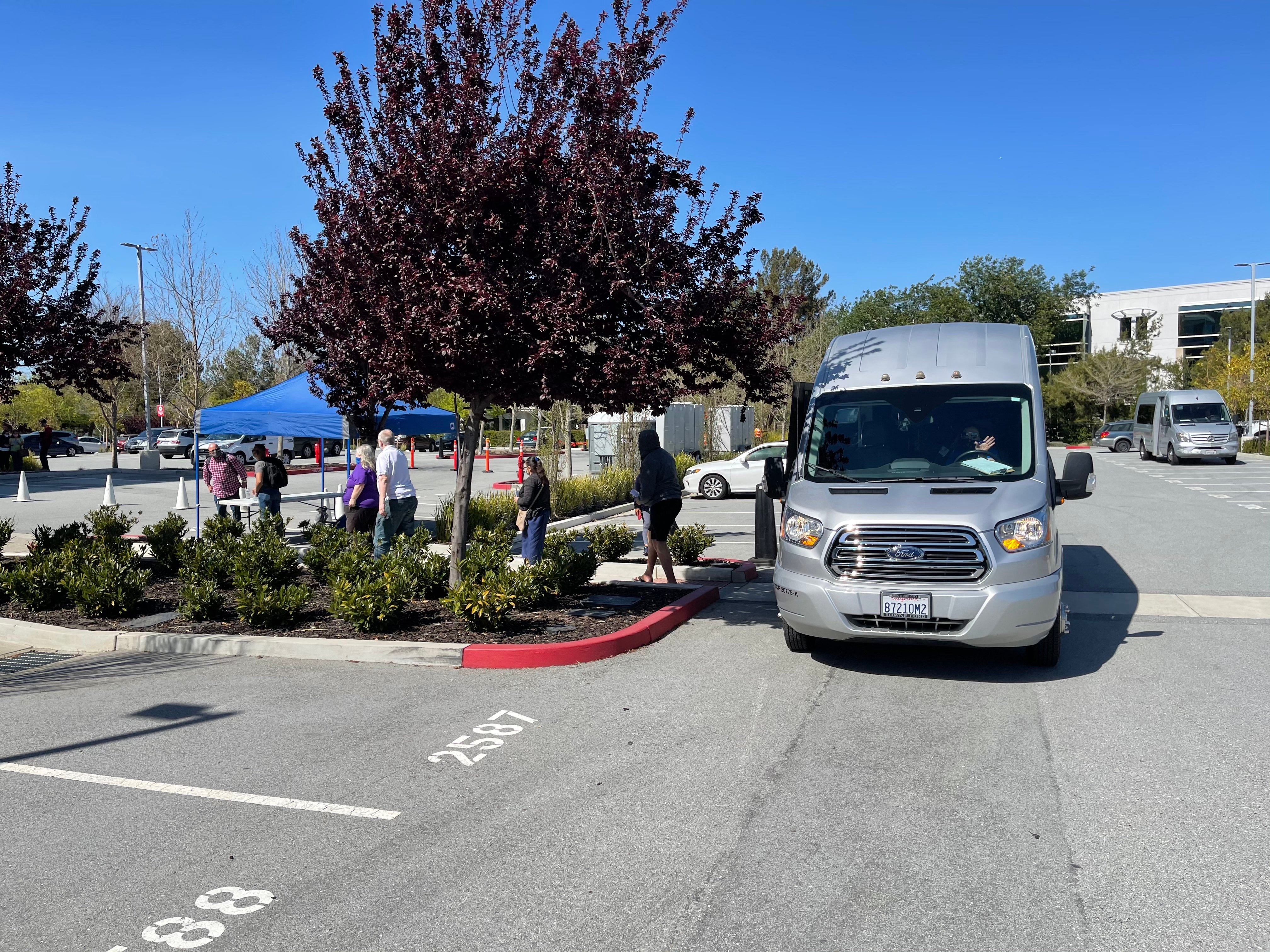 Shuttle in parking lot in front of a tent with a line of people